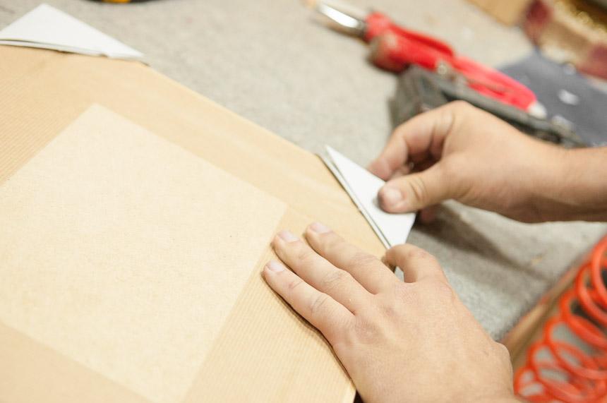 Se protege el marco con esquinas de cartón para asegurar su ...